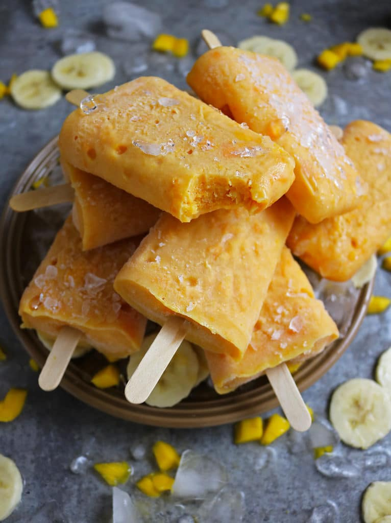 Bite of Mango And Banana Protein Popsicles on Plate