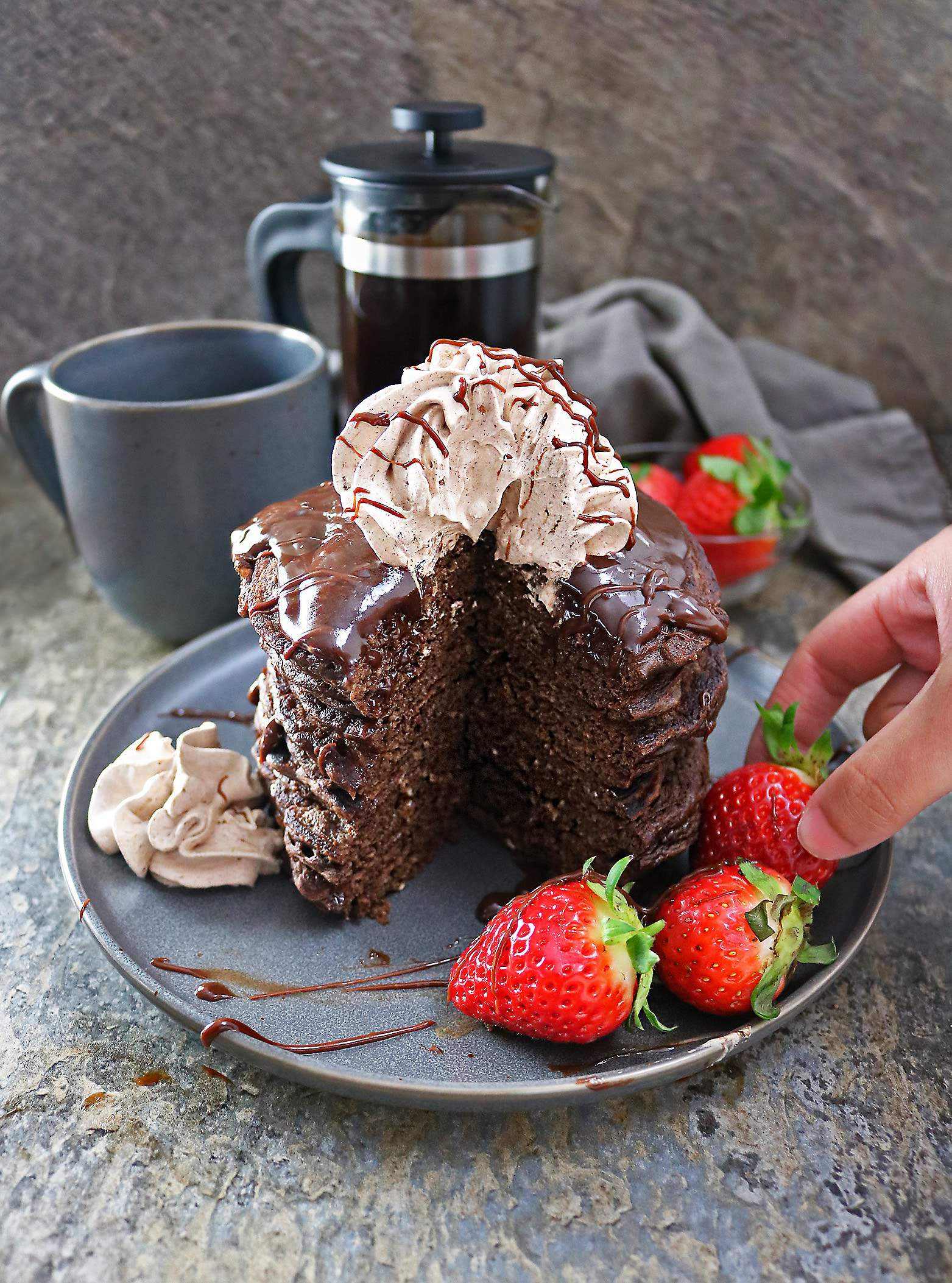 Easy Chocolate Coffee Pancakes with Chocolate Sauce and chocolate whipped cream and strawberries