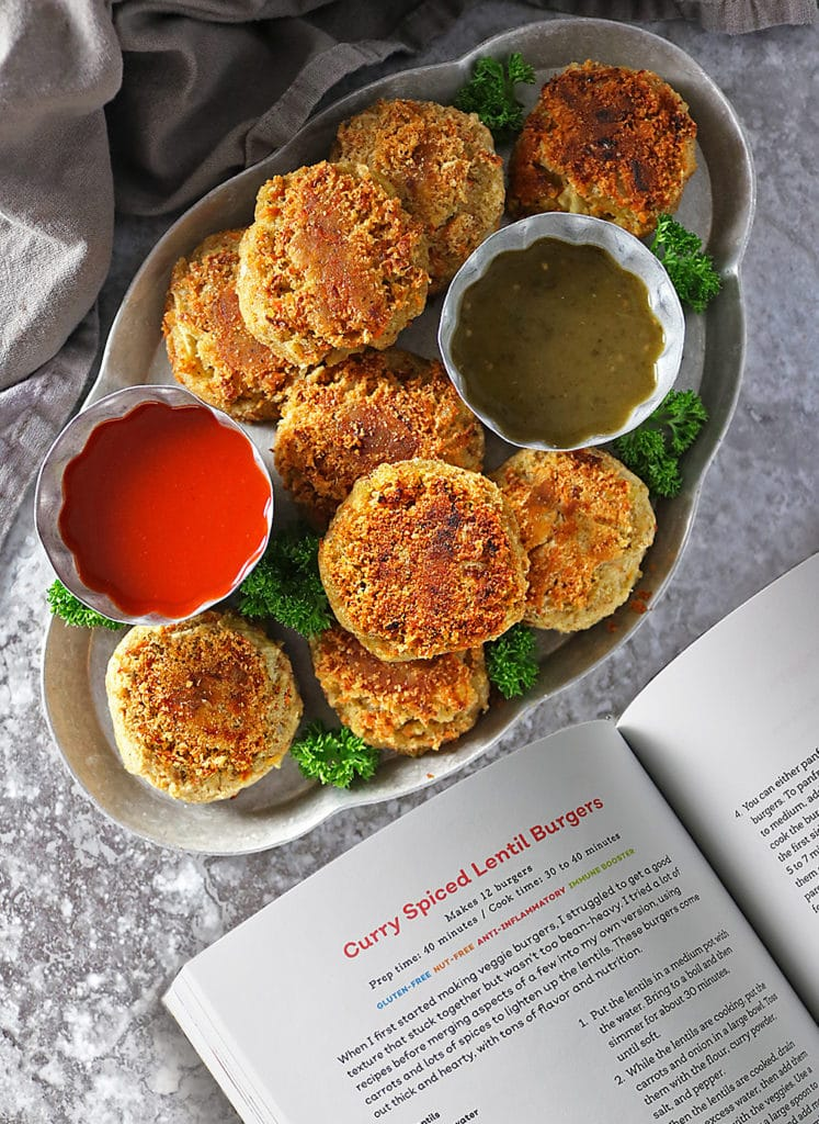 Overhead photo os angled container with Lentil Burgers and dipping sauces with napkin with open cookbook