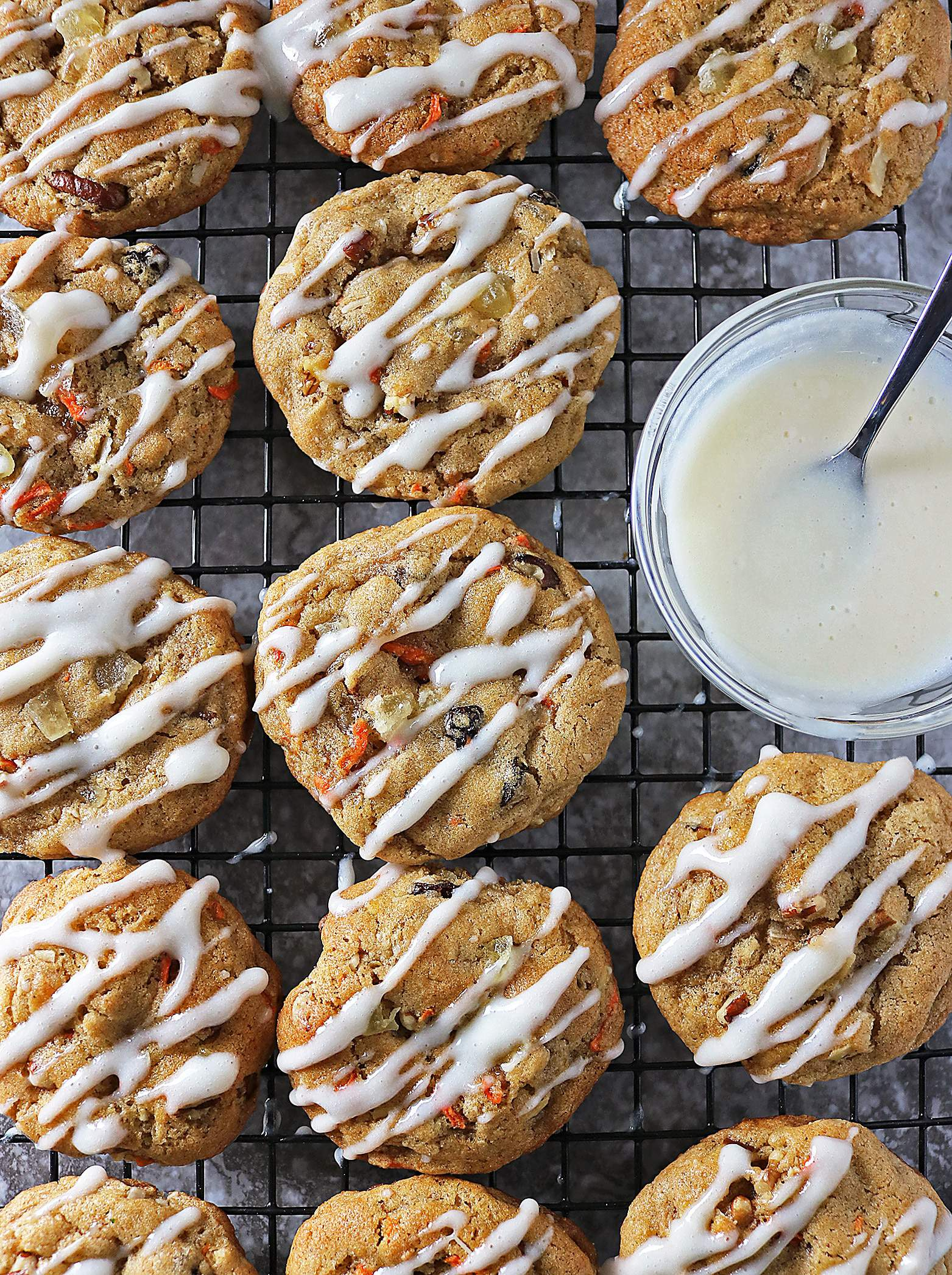 Chock full of carrots, walnuts, raisins, cardamom, cinnamon and candied pineapple, these Carrot Cake Cookies with Cream Cheese Drizzle are heavy on flavor.