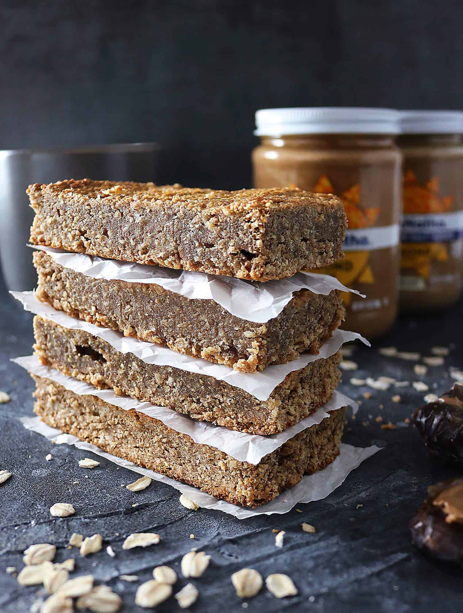 Stack of four Date Almond Bars with almond butter jars in the background.