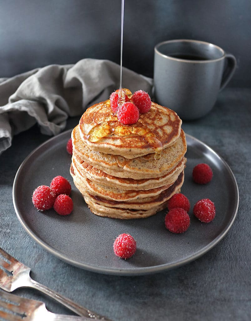 Stack of Almond Hemp Pancakes with honey drizzle and coffee cup