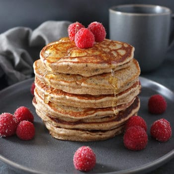 Stack of four Almond Hemp Pancakes with raspberries