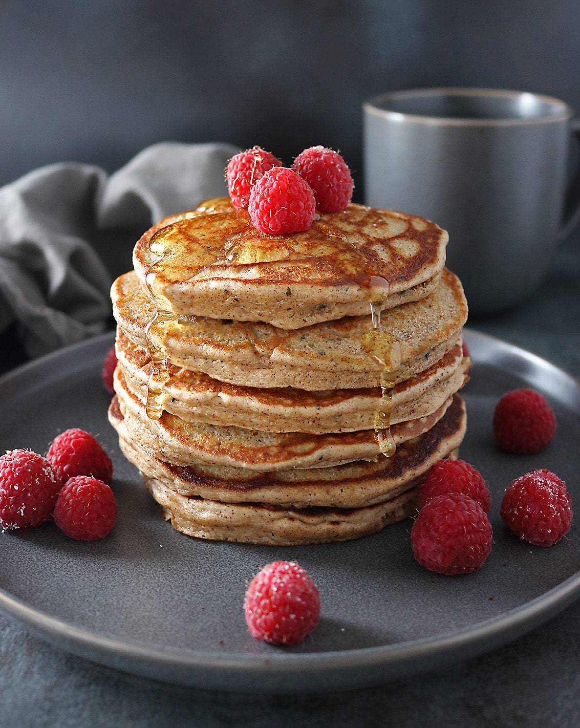 Stack of four Almond Hemp Pancakes with raspberries