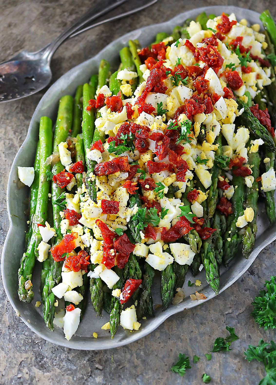 Sauteed Asparagus topped with boiled egg and sundried tomatoes on a silver platter
