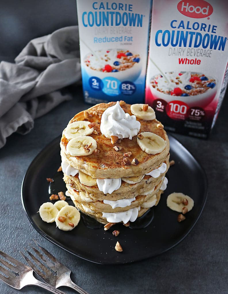Stack of Pecan Banana Pancakes with layers of bananas and whipped cream and Hood Calorie Countdown in the background