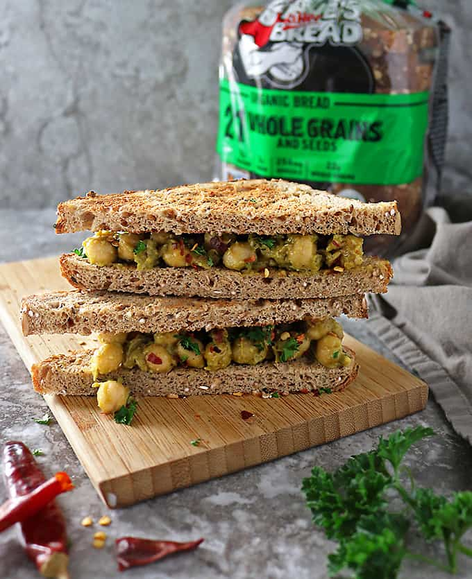 Two stacked cut sandwiches with chickpea avocado salad and Dave's Killer Bread in the background