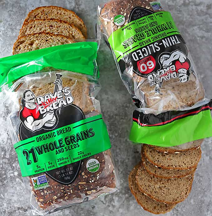Two loaves of Dave's Killer Bread 21 Whole Grains and Seeds opened with slices peeking out