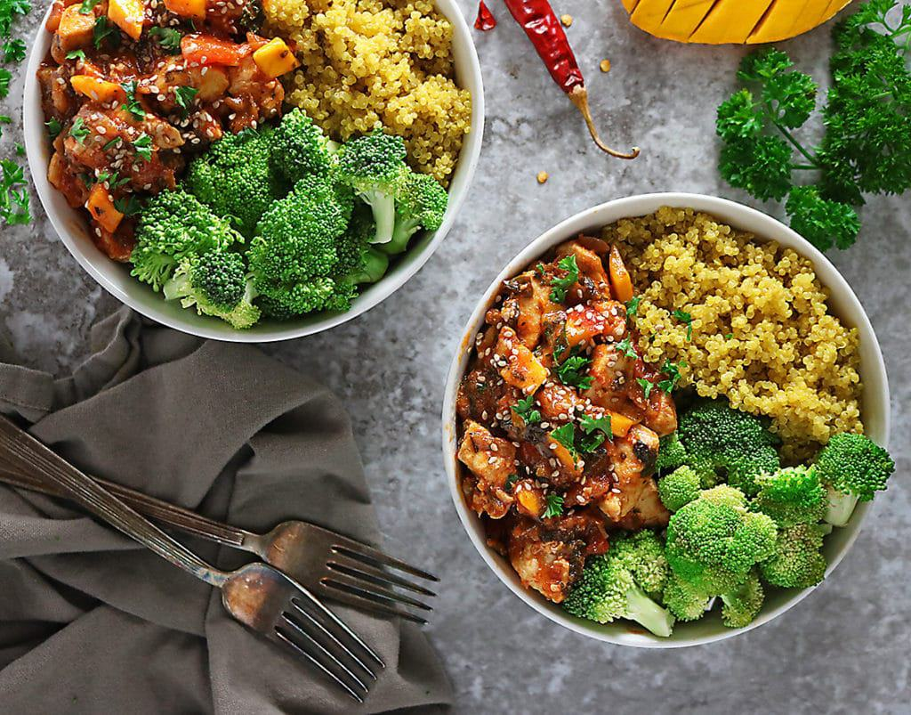 Two bowls of mango chicken with turmeric quinoa and steamed broccoli