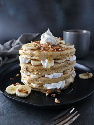 Stack of Pecan Banana Pancakes with layers of bananas and whipped cream