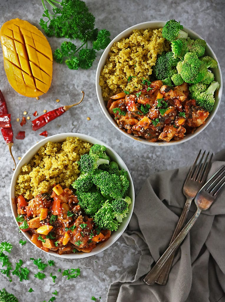 Overhead photo of 2 bowls with mango chicken, turmeric quinoa and broccoli with cut mango and parsley and chili flake garnish