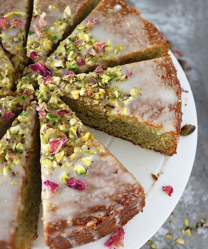 Overhead photo of Ottolenghi's Pistachio Rose Semolina Cake cut into slices