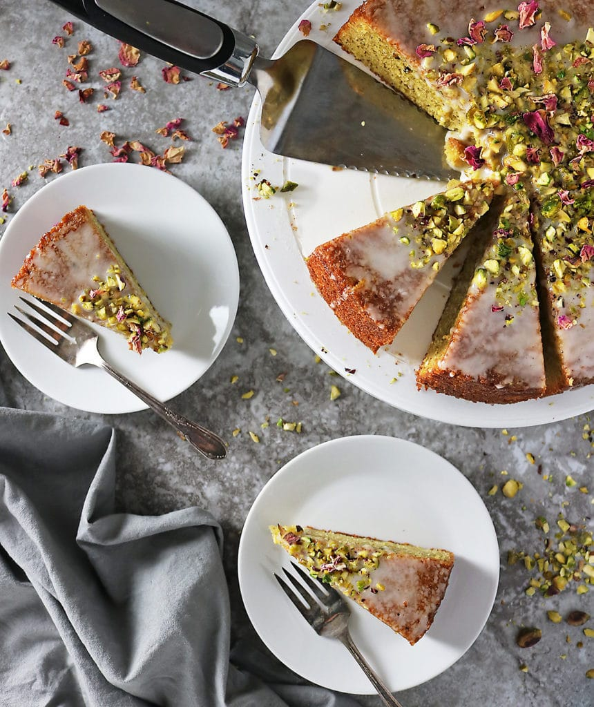 Overhead photo of Ottolenghi's Pistachio Rose Cake with two slices on dessert plates with forks