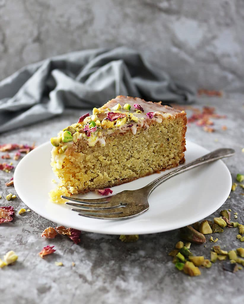 A Slice of Ottolenghi's Pistachio Rose Cake on a plate with a fork