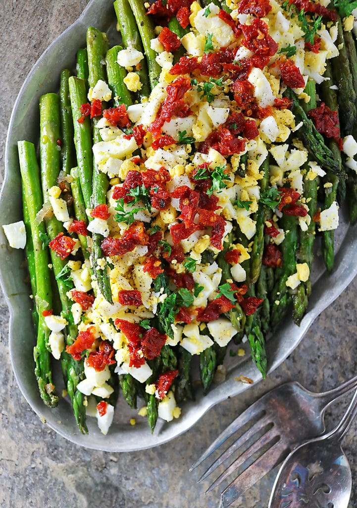 Overhead photo of Sauteed Asparagus, boiled egg and sundried tomatoes in a platter
