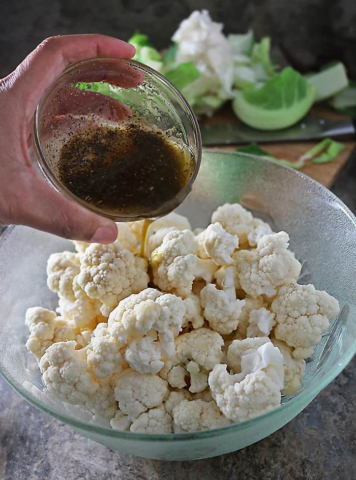 Cauliflower being tossed with olive oil, oregano and coriander