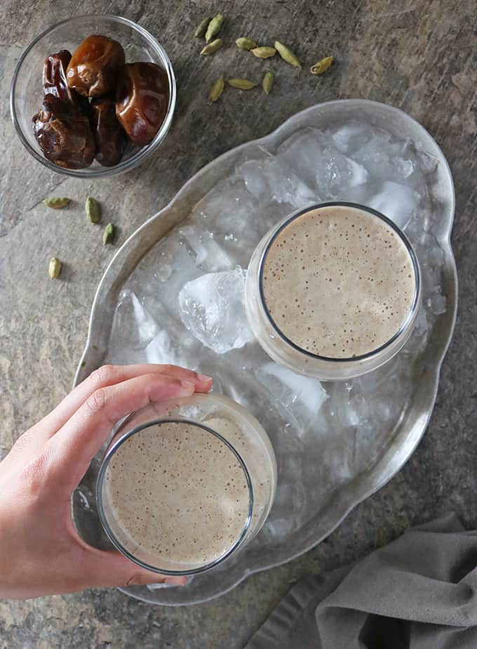Overhead photo of hand reaching for 1 of 2 glasses with date shake in them