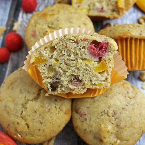 Photo of A Gluten Free Nutty Vegan Peach Raspberry Muffin cut in half with other whole ones