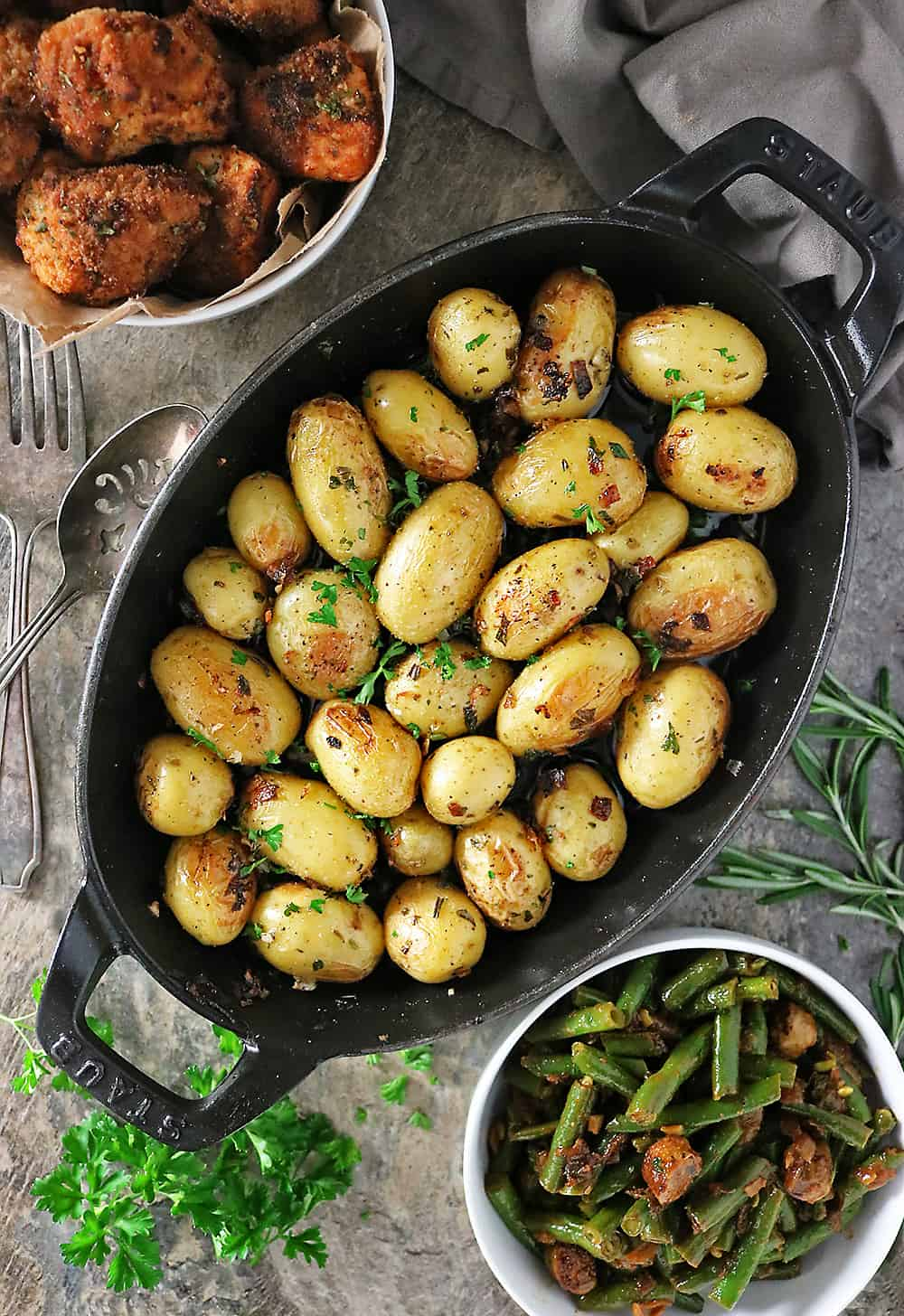 Cast-iron herb garlic potatoes, beans and sausage and fried baked chicken photo