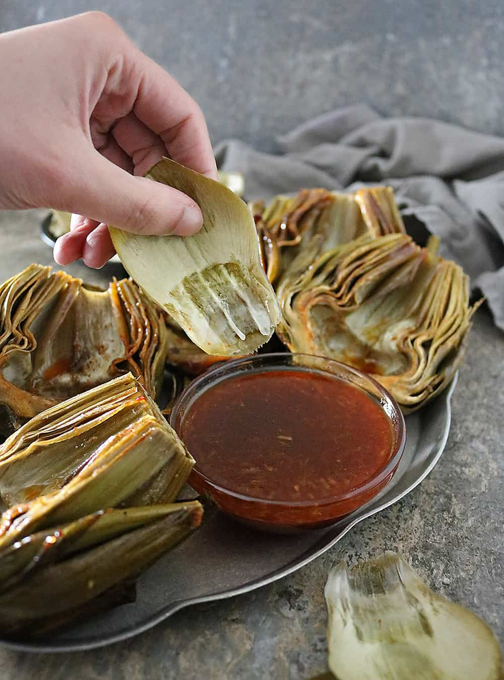 Delicious fresh artichokes are cleaned, trimmed, de-choked, and slathered with a tastebud tantalizing, Honey Orange Chili Sauce and oven roasted into a side your friends and family are so to get a kick out of!
