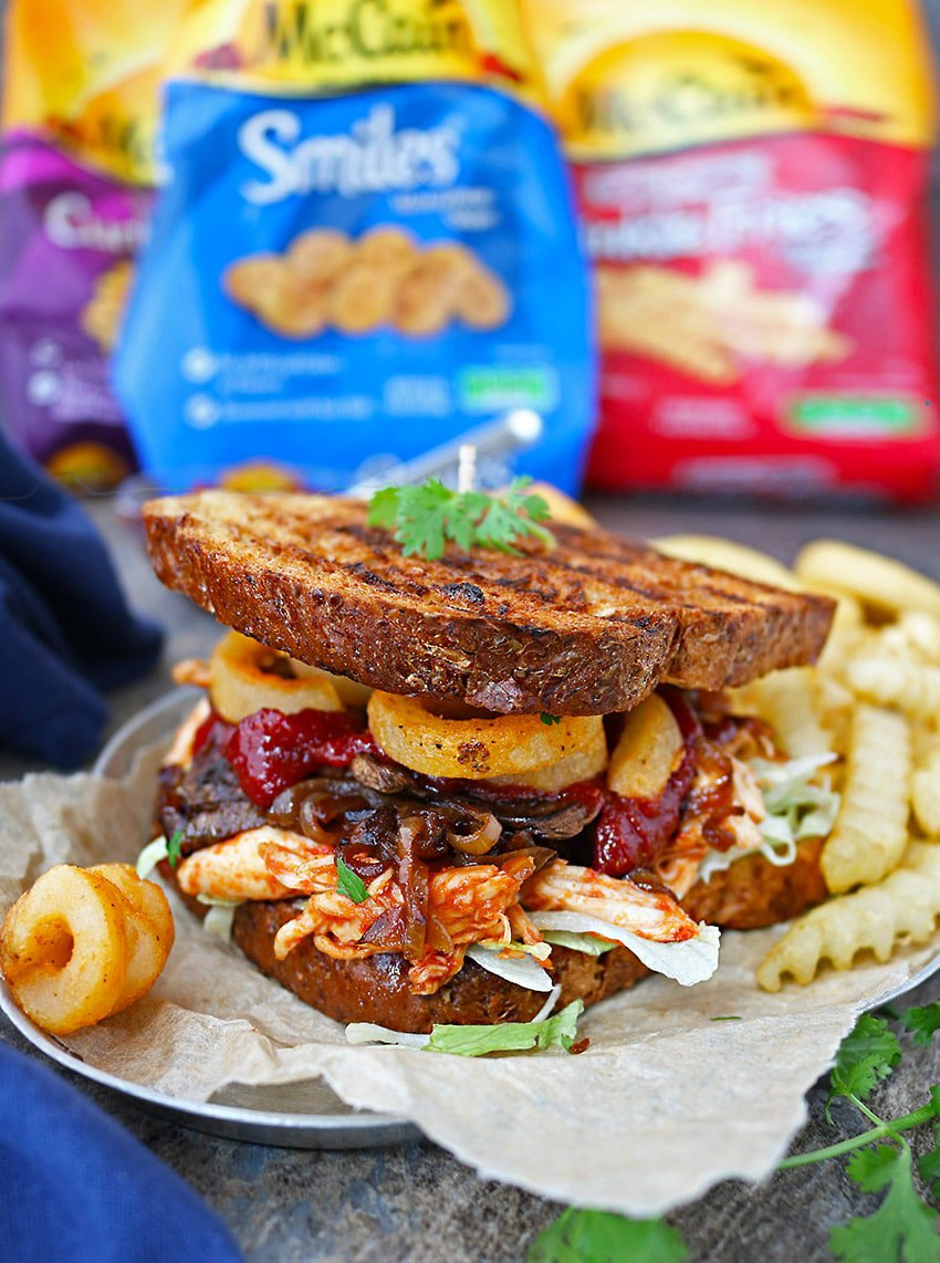 This piled-high Sweet Spicy Chicken Fries Sandwich has shredded lettuce, tender shredded chicken (that was marinated and cooked in an easy sweet spicy sauce), caramelized onions, crispy mushrooms, McCain® Seasoned Curly Fries Seasoned Potato Fries, and McCain® Smiles® Mashed Potato Shapes.