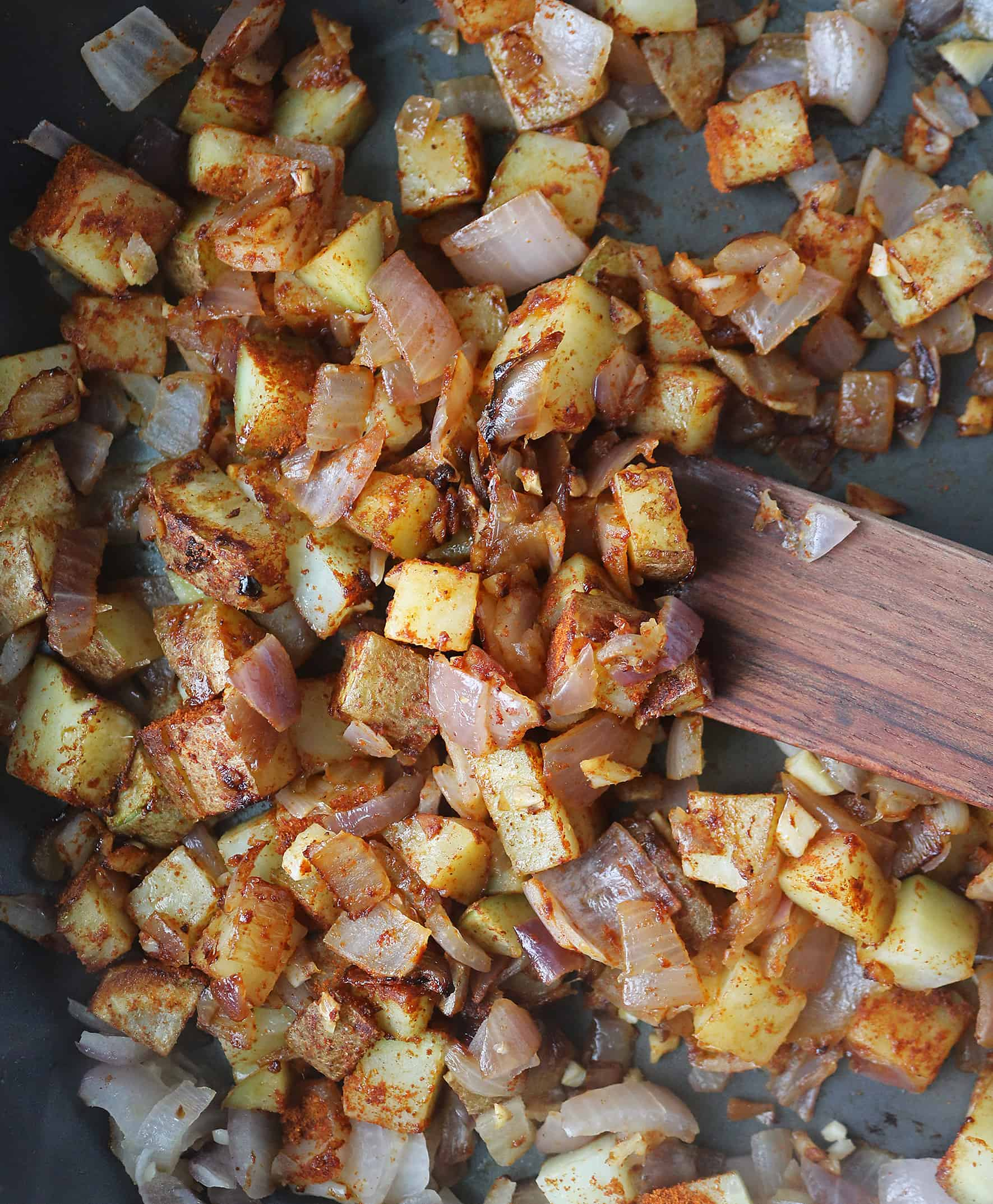 Cubed potatoes being sauteed with onions, garlic, ginger and Berbere seasoning.