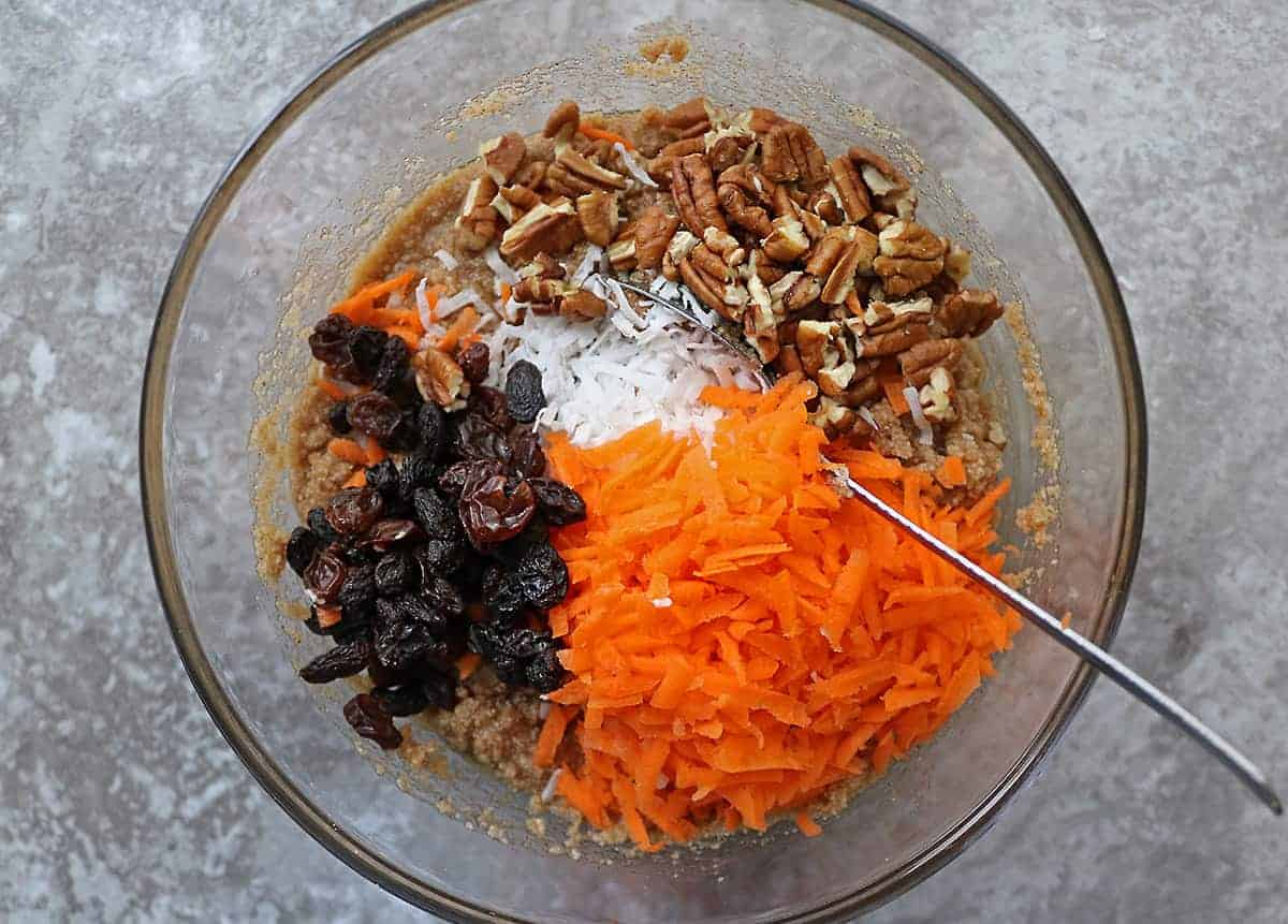 Mixing ingredients like carrots, raisins and walnuts for paleo carrot cake bars