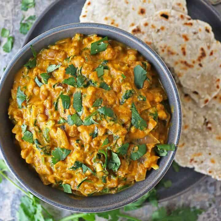 Easy vegan lentil curry in a bowl with Sri Lankan roti in a plate near by.