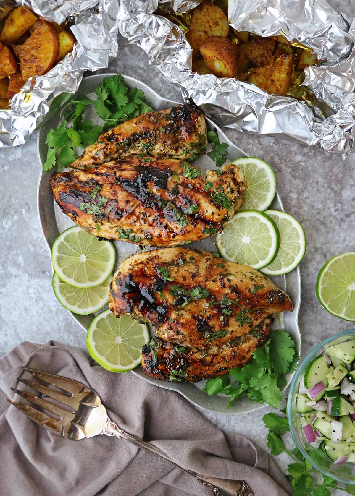 Table with Mouthwatering grilled cilantro lime chicken with turmeric potatoes and easy cucumber salad