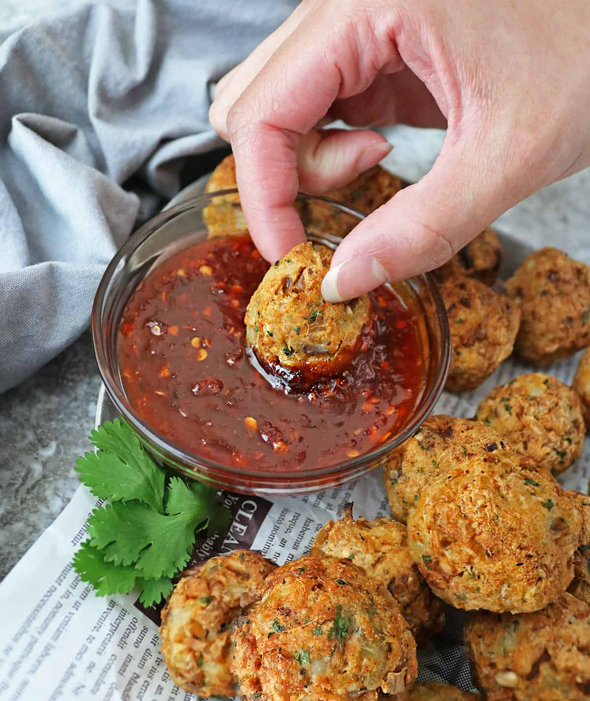 Air fryer salmon croquettes dipped into sweet chili sauce.