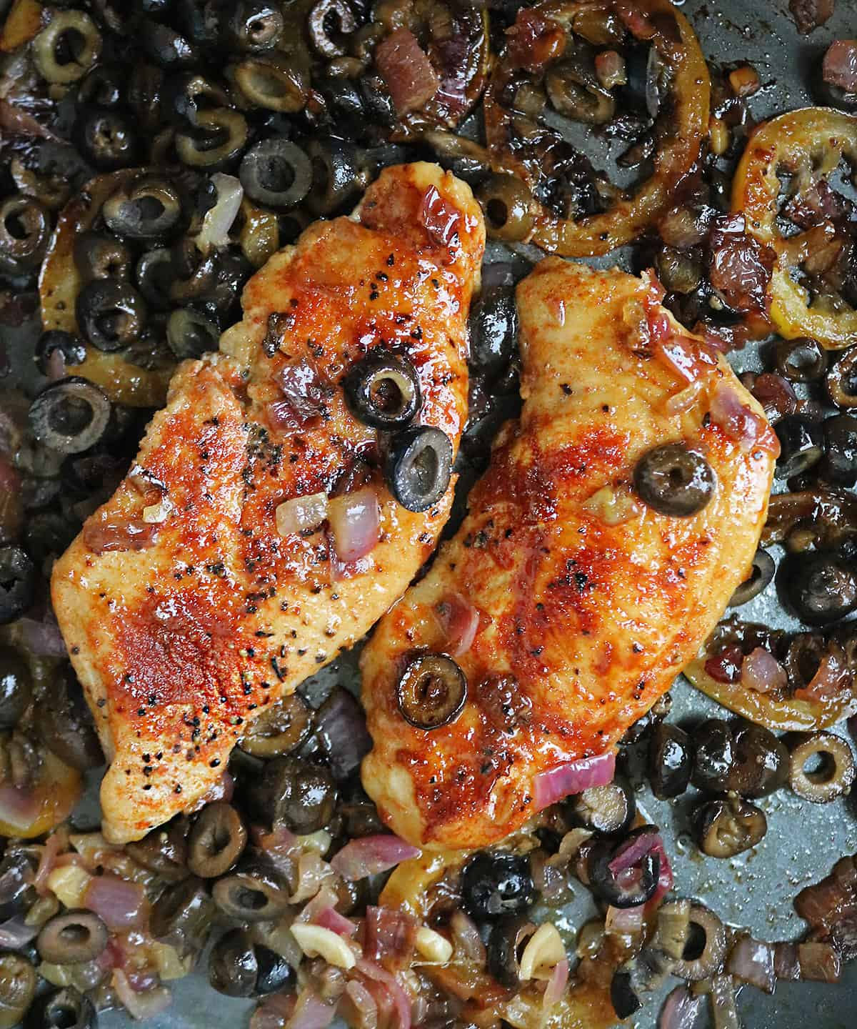 Delicious honey lemon chicken sauteing in pan with olives and caramelize lemon slices