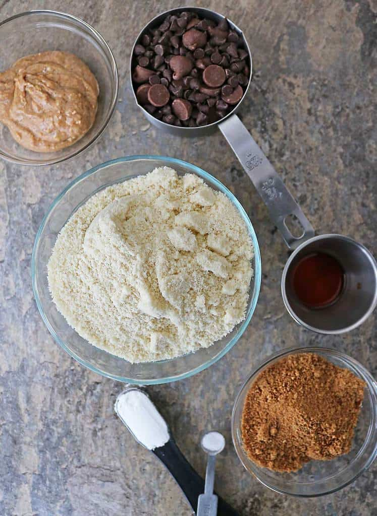 Ingredients to make almond chocolate-chip cookies in a flat lay