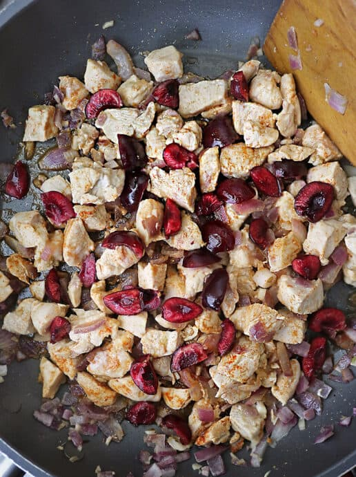 Sauteing Chicken With Cherries in a pan.