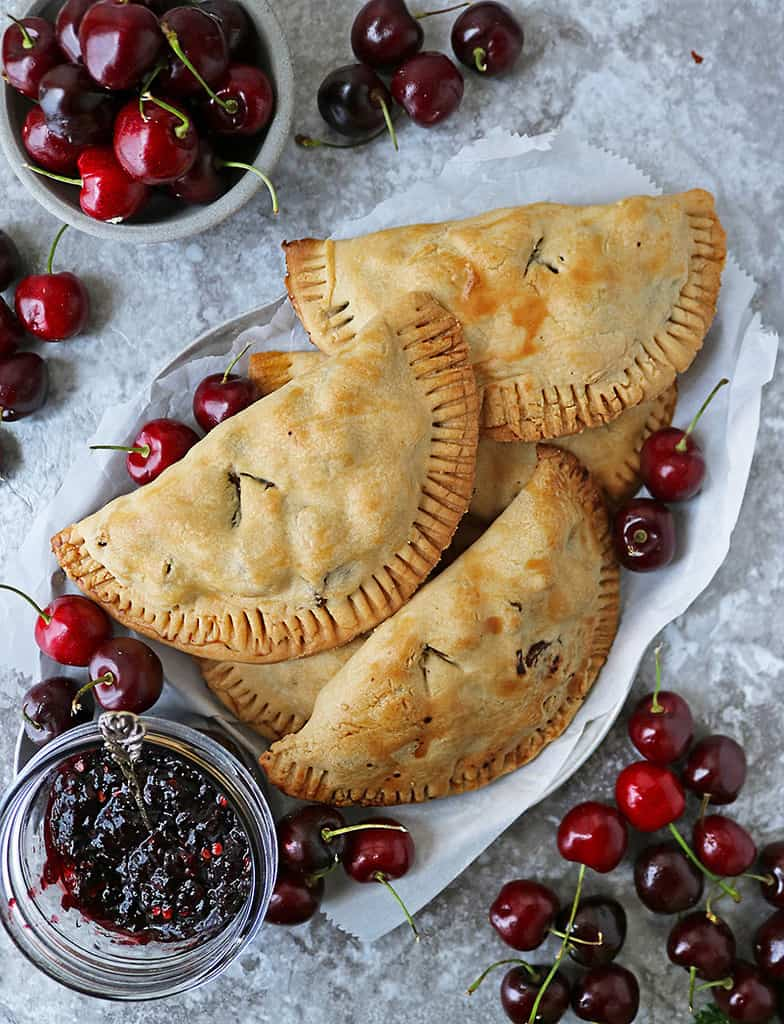 A plate of Savory cherry hand pies with chicken along with fresh cherries scattered around.