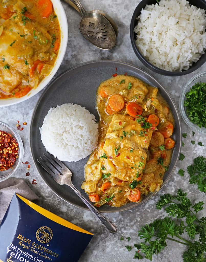 Plate with rice and Yellow fish curry on it.