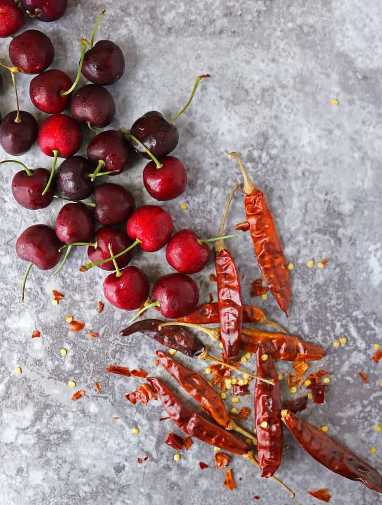 gray board with cherries and chilies