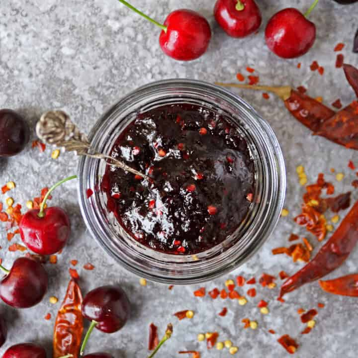 jar with delicious easy chili cherry sauce and cherries and whole chilies scattered around it.