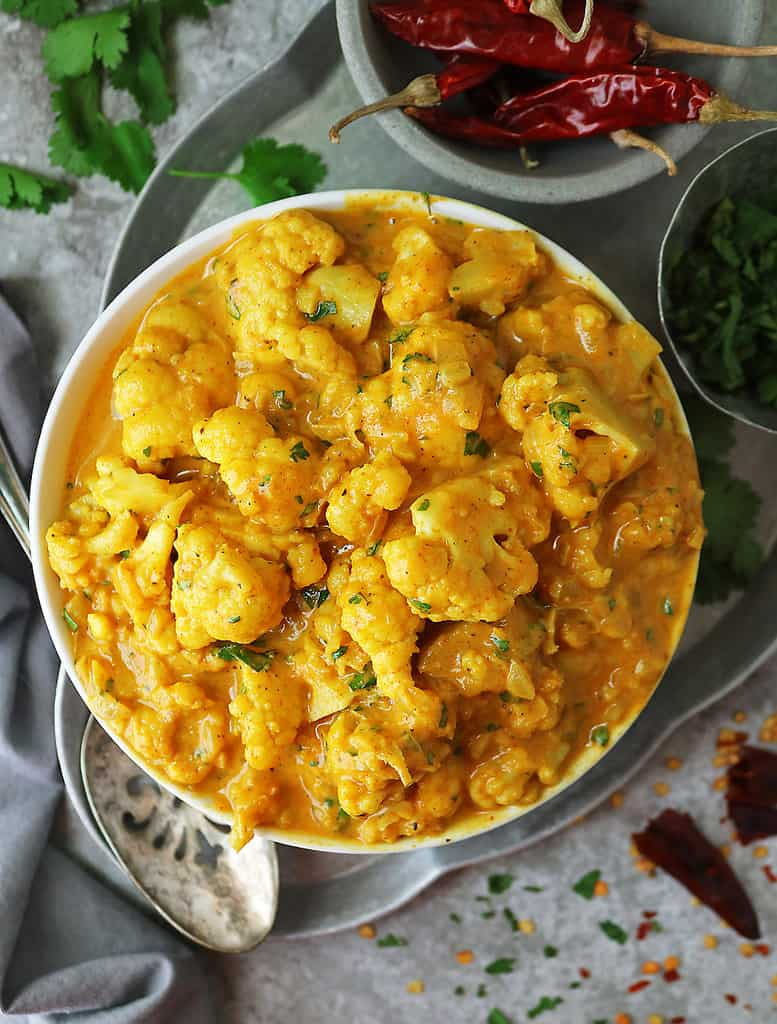 Easy Vegan Cauliflower Curry With Pumpkin in a bowl with condiments by its side.