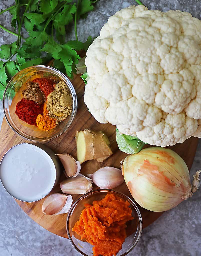 Ingredients to make cauliflower pumpkin curry on a cutting board.