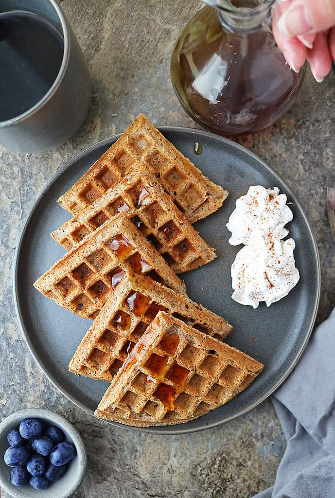 A plate of vegan waffles with maple syrup and a cup of coffee.