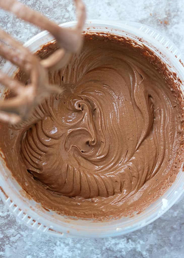 Using an electric mixer to mix the ingredients for this vegan chocolate ice cream.