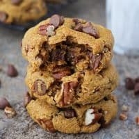3 Easy pumpkin chocolate chip cookieswith a bite taken out of one and a glass of cold milk in the background.