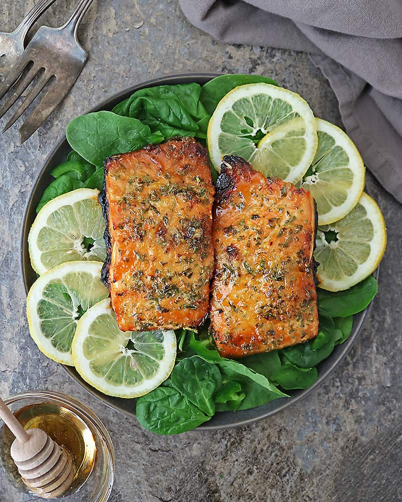 Plate with Tasty and easy Air Fryer Honey Salmon on a bed of spinach.