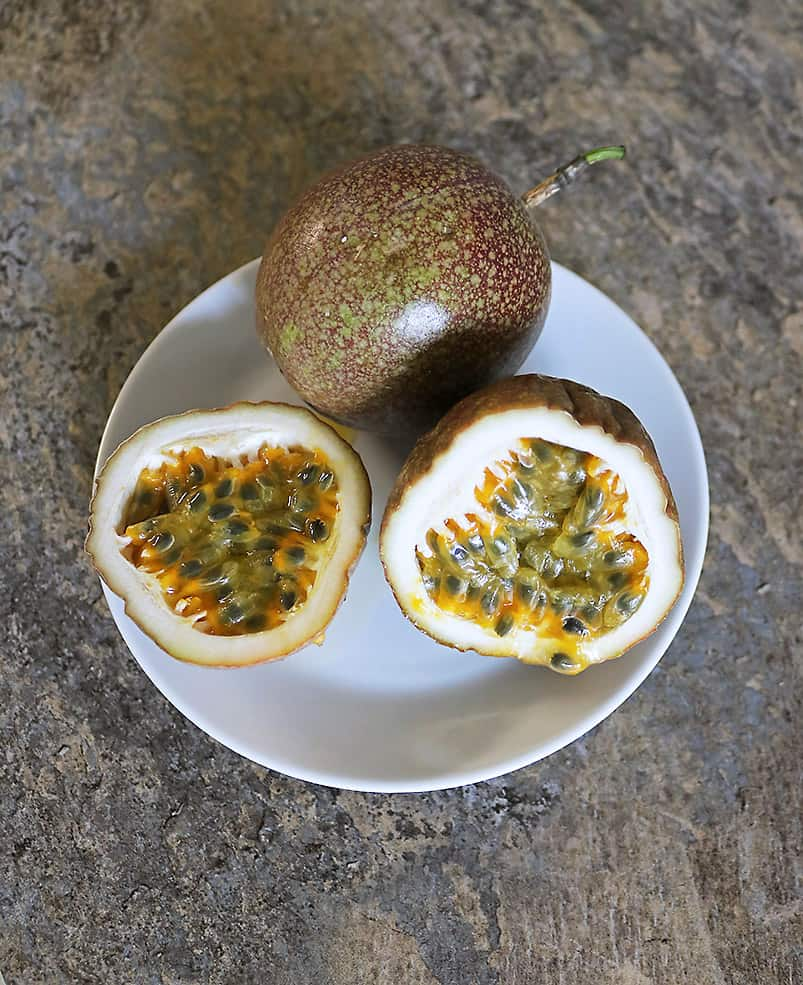 Tasty passion fruit cut in half on a plate next to a whole passion fruit.