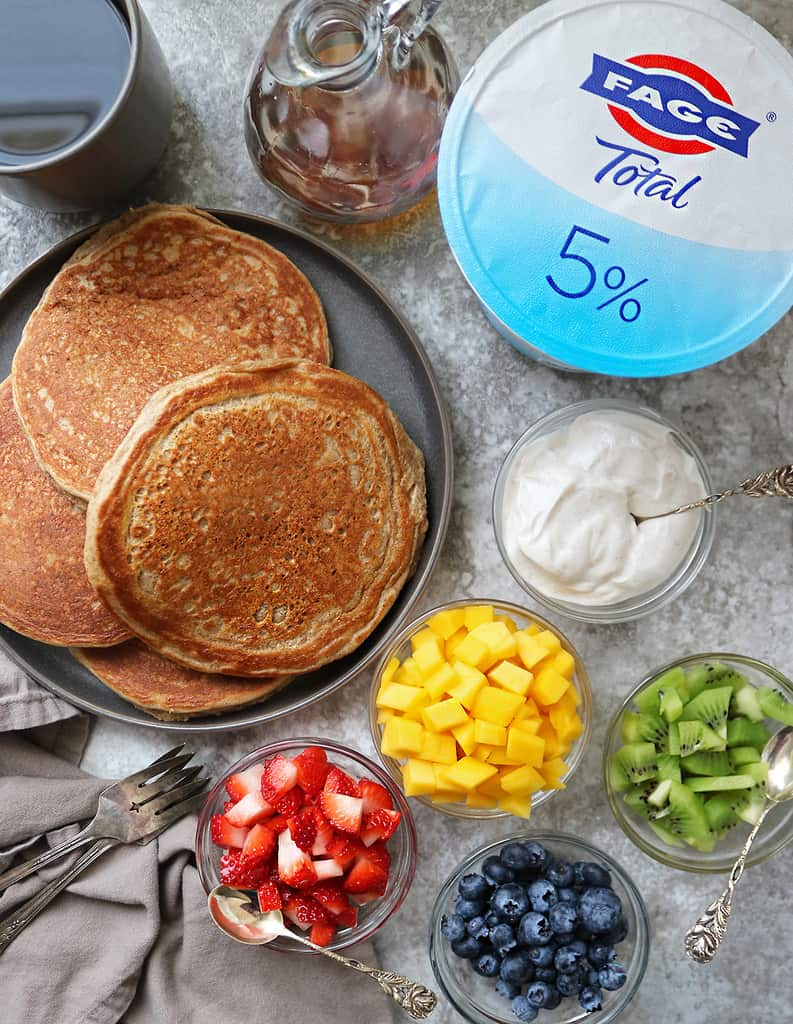 Tasty gluten free yogurt pancakes with bowls of fruit and fage laid out on a table.