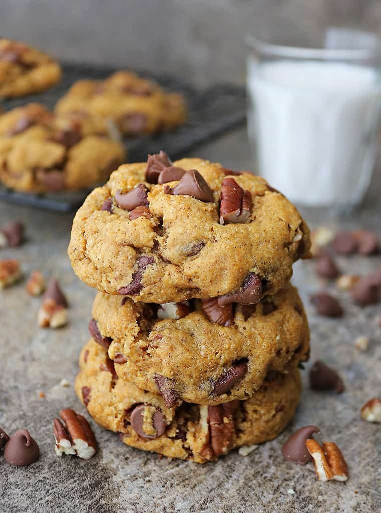 stack of 3 pumpkin chocolate chip cookies dairy-free with a glass of milk in the background.