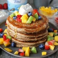 stack of gluten free yogurt pancakes with yogurt topping and fruit and FAGE.