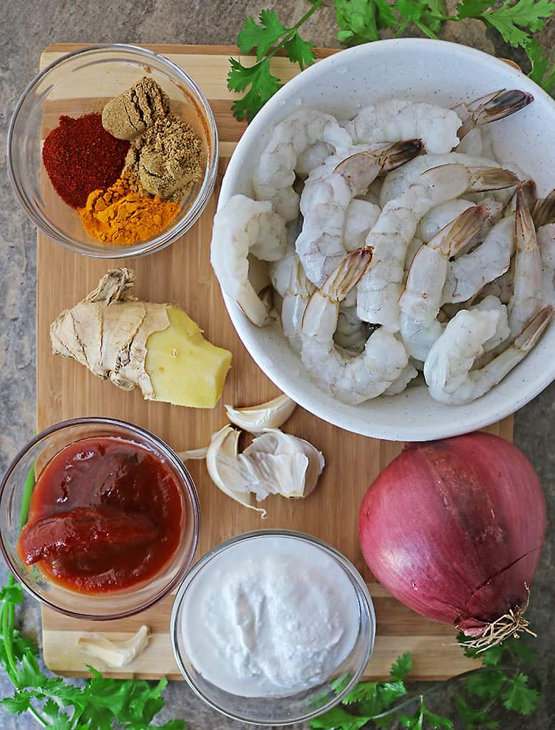 Ingredients to make shrimp curry on board on a flatlay
