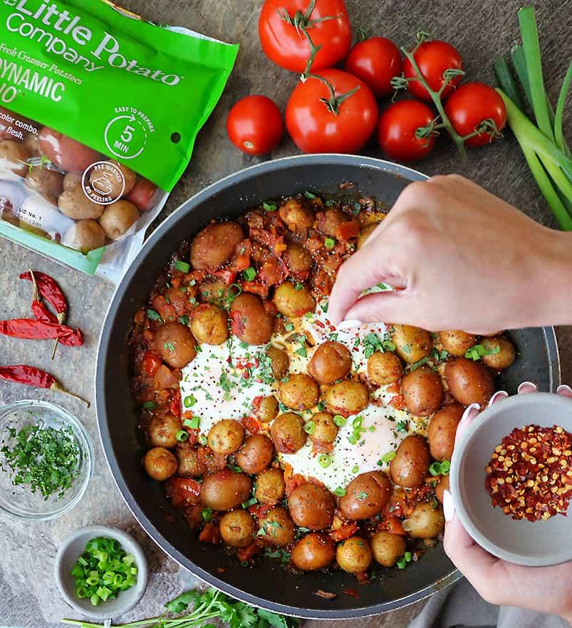 Garnishing potato shakshuka made with Little Potato Company Dynamic Dou Potatoes