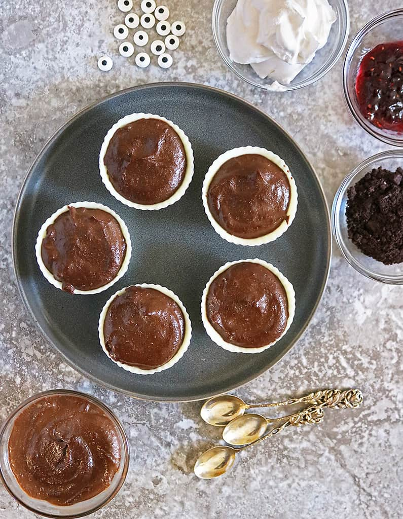Plate of chocolate cashew pudding filling in white chocolate cups